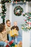 Glückliche Familie umgeben durch Weihnachtsgeschenke stockbild