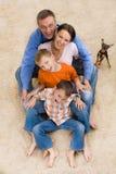 Glückliche Familie und Hund auf dem Teppich Stockbilder
