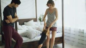 Glückliche Familie und kleines nettes Tochtertanzen und um nahes Bett im Schlafzimmer zu Hause sich drehen stock video footage