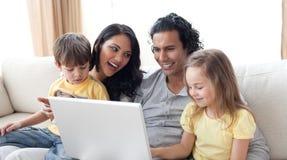 Glückliche Familie unter Verwendung des Laptops auf Sofa Stockbild