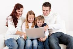 Glückliche Familie unter Verwendung des Laptops zu Hause Stockbilder