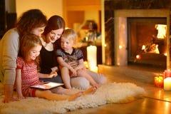 Glückliche Familie unter Verwendung eines Tabletten-PC durch einen Kamin Stockfotos