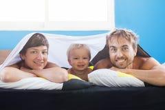Glückliche Familie - Vater-, Mutter- und Kleinkindjunge auf Bett unter dem Blatt, wachte und Lächeln, Wochenendenmorgen auf lizenzfreies stockbild