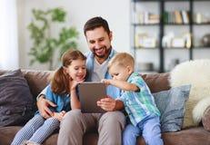 Glückliche Familie Vater und Kinder mit Tablet-Computer zu Hause stockbilder