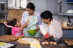 Glückliche Familie von mehreren Generationen, die Lebensmittel zubereitet lizenzfreies stockfoto