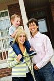 Glückliche Familie vor Haus Stockbild