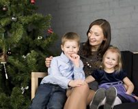 Glückliche Familie am Weihnachtsbaum Stockfotos