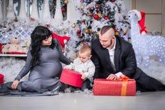 Glückliche Familie Weihnachtsoffenes Geschenk schwangerer Mutter lizenzfreie stockbilder