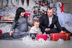 Glückliche Familie Weihnachtsoffenes Geschenk schwangerer Mutter lizenzfreies stockbild