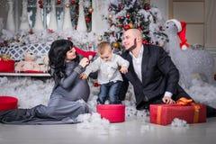 Glückliche Familie Weihnachtsoffenes Geschenk schwangerer Mutter stockbilder