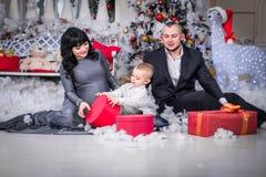 Glückliche Familie Weihnachtsoffenes Geschenk schwangerer Mutter lizenzfreies stockfoto