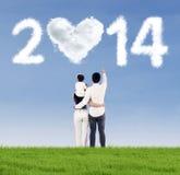 Glückliche Familie, welche die Zukunft von 2014 betrachtet Stockfotos
