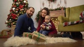 Glückliche Familie, welche zusammen die Weihnachtsmutter, Vater und kleines Baby sitzen auf dem Boden im Raum mit feiert stock video