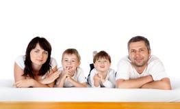 Glückliche Familie zusammen auf Bett Stockbild