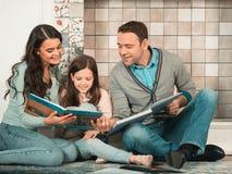 Glückliche Familie zusammen gelesen lizenzfreie stockfotografie