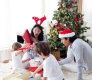 Glückliche Familienöffnung Weihnachtsgeschenke Stockfotos