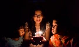 Glückliche Familien-Schlagkerzen auf Geburtstags-Kuchen Stockfoto