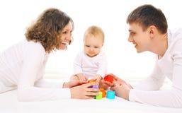 Glückliche Familieneltern und -baby, die mit Spielwaren spielt Stockfotografie