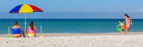 Glückliche Familieneltern und -kinder, die Spaß in den Klappstühlen auf einem Strand haben stockfotografie