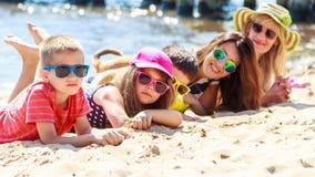 Glückliche Familienfrauenkinder, die auf Strand ein Sonnenbad nehmen Lizenzfreie Stockfotos