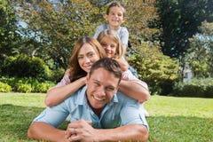 Glückliche Familienmitglieder, die auf einander liegen Stockfotografie