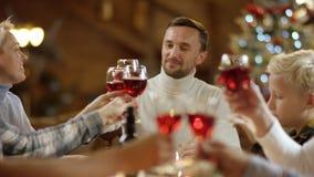 Glückliche Familienmitglieder klirrt ihre Gläser und Getränke durch Weihnachtstabelle stock video