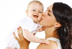 Glückliche Familienmutter, die Baby küsst Stockfotos