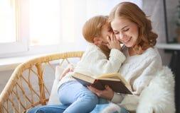 Glückliche Familienmutter liest Buch zum Kind zur Tochter durch Fenster lizenzfreies stockfoto