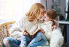 Glückliche Familienmutter liest Buch zum Kind zur Tochter durch Fenster stockbilder