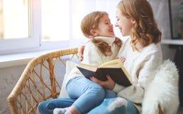 Glückliche Familienmutter liest Buch zum Kind zur Tochter durch Fenster lizenzfreies stockbild