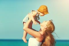 Glückliche Familienmutter mit Babysohn geht durch Ozean auf Strand in der Summe stockbild
