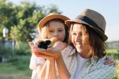 Glückliche Familienmutter mit Tochter in der Natur, Frau, die kleine neugeborene Babyküken in den Händen, Bauernhof, rustikale Ar stockfoto