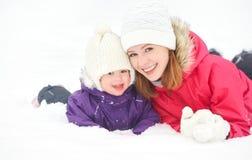 Glückliche Familienmutter und Babytochter, die im Winterschnee spielt und lacht Lizenzfreie Stockbilder
