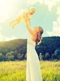 Glückliche Familienmutter und Babytochter spielen auf Natur Stockfotos