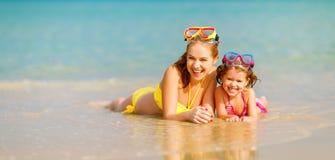 Glückliche Familienmutter und chid Tochter in den Masken auf Strand im summe Stockbild