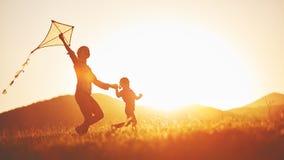 Glückliche Familienmutter und -kind laufen auf Wiese mit einem Drachen im s Lizenzfreies Stockfoto