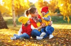 Glückliche Familienmutter und -kinder auf Herbst gehen stockbild