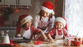 Glückliche Familienmutter und -kinder backen Plätzchen für Weihnachten stockbild