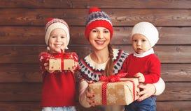 Glückliche Familienmutter und -kinder mit Weihnachtsgeschenk an hölzernem b Lizenzfreies Stockbild