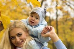 Glückliche Familienmutter und Kindertochter, die auf Herbstweg spielt und lacht Lizenzfreie Stockfotos