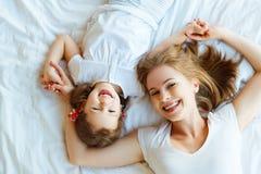 Glückliche Familienmutter und Kindertochter lachen im Bett stockfotografie