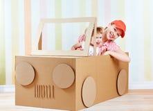 Glückliche Familienmutter und kleine Tochter fahren auf das Spielzeugauto, das von der Pappe hergestellt wird Lizenzfreies Stockfoto