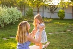 Glückliche Familienmutter und -tochter, die im Sommer auf der Natur umarmt Stockbild