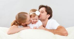 Glückliche Familienmutter, Vater, Kinderbabytochter zu Hause auf dem spielenden Sofa und Lachen Stockbild