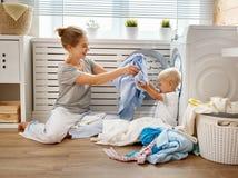 Glückliche Familienmutterhausfrau und Babysohn in der Wäscherei laden lizenzfreies stockfoto