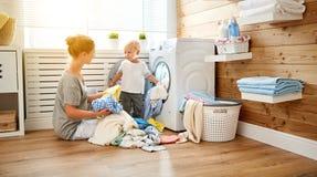 Glückliche Familienmutterhausfrau und -kinder in der Wäscherei laden w stockbilder