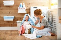 Glückliche Familienmutterhausfrau und -kinder in der Wäscherei laden w lizenzfreies stockfoto