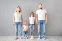 Glückliche Familienstellung gegen grauen Hintergrund lizenzfreie stockfotografie