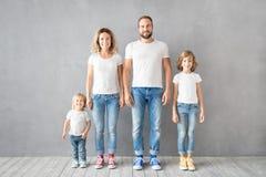 Glückliche Familienstellung gegen grauen Hintergrund lizenzfreie stockbilder