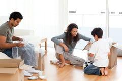 Glückliche Familienverpackung richtet zusammen an stockfotografie